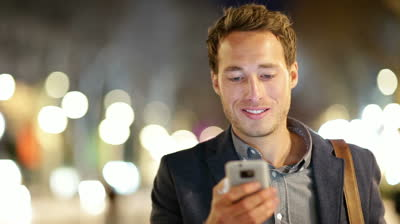 stock-footage-man-sms-texting-using-app-on-smart-phone-at-night-in-city-handsome-young-business-man-using
